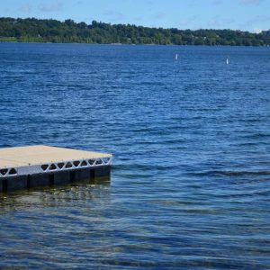 End of a CanadaDocks floating dock in a deep blue lake