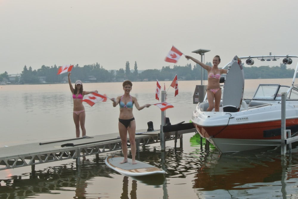 Girls waving Canadian flags on the boat, board and dock