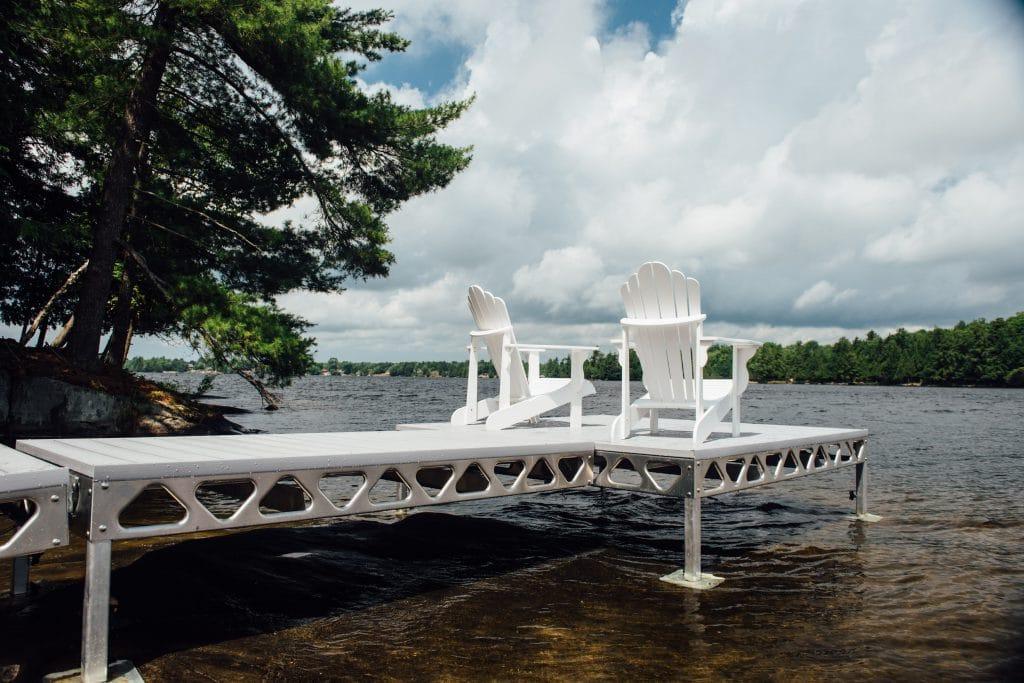 Two white muskoka chairs on CanadaDocks dock with AlphaDeck decking.