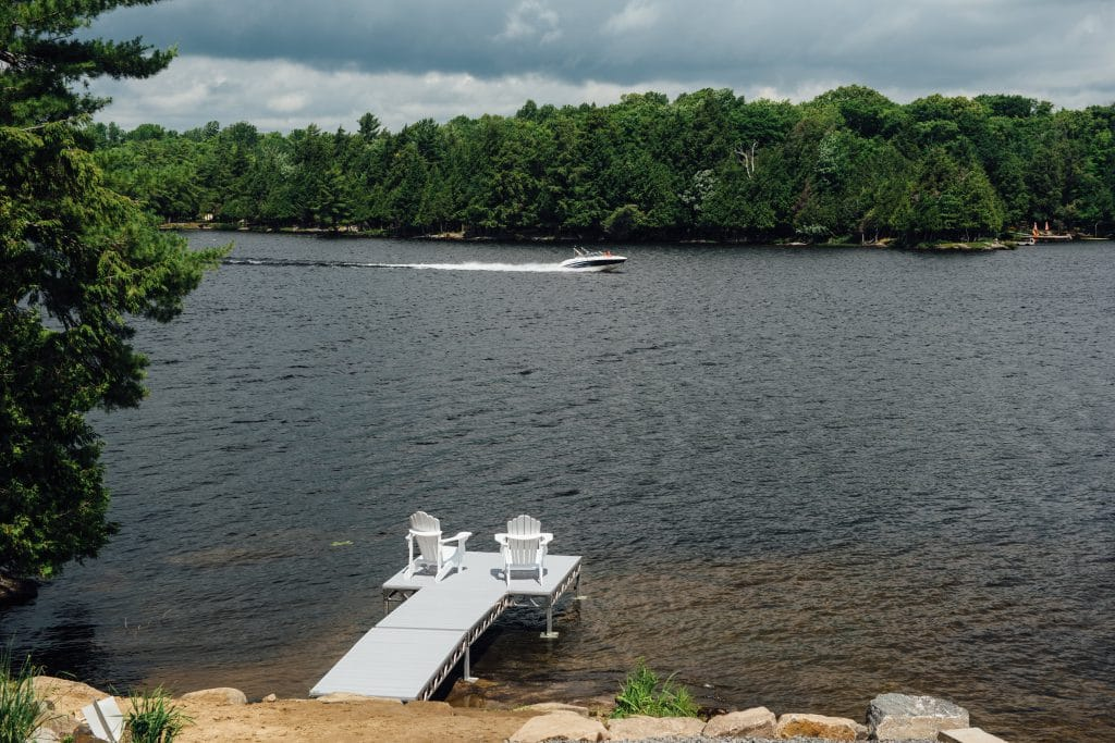 CanadaDocks standing dock configuration with gray AlphaDeck decking with boat zooming by.