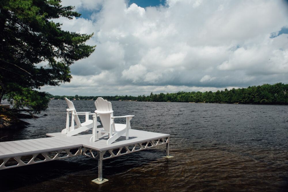 Two white muskoka chairs on AlphaDeck decking installed on a standing CanadaDocks configuration.