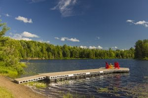 CanadaDocks Floating Dock with Hexagon end and muskoka chairs on a scenic lake