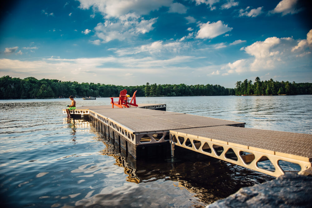 CanadaDocks Ramp and Floating Dock with muskoka chairs and kid fishing