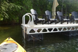 A row of muskoka chairs on a CanadaDocks floating dock with ladder